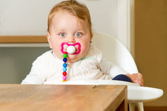 Smiling baby with soother. Curious baby with soother looking in to the camera Royalty Free Stock Images