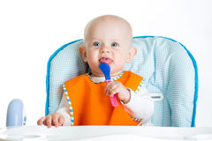 Smiling baby with spoon waiting food Stock Photo