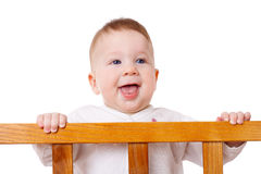 Smiling baby standing in bed. Smiling baby with slobber on face is standing in the bed, isolated on white Stock Image