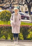 Full body of cheerful beautiful business woman. Smiling baby on the street in a pink autumn coat Royalty Free Stock Photos