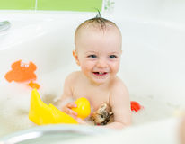 Smiling baby taking bath and playing toys Royalty Free Stock Image