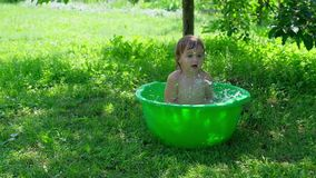Smiling baby taking a bath and splashing with two hands in small bathtub. Outdoor baby bathing. smiling baby taking a bath and splashing with two hands in small stock video