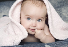 Smiling baby with a towel. Cute smiling baby girl with a pink towel royalty free stock photo
