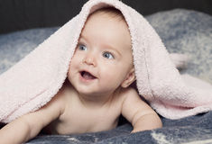 Smiling baby with a towel Stock Image