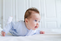 Smiling baby tummy time in a white nursery Stock Photography