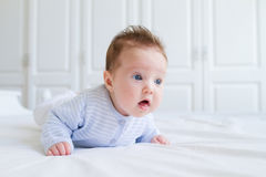 Smiling baby tummy time in a white nursery Royalty Free Stock Image