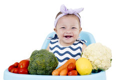 Smiling baby with vegetables on chair Stock Photo