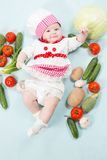 Smiling baby wearing a chef hat surrounded by vegetables Stock Image
