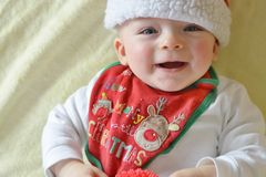 Smiling baby wearing Christmas bib and cap Stock Images