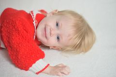 Smiling baby on a white blanket Stock Images