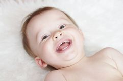 Smiling baby on white plaid. Smiling baby age of 11 months on white plaid Royalty Free Stock Photos