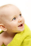 Smiling baby wrapped in a green towel Royalty Free Stock Photos