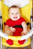 Smiling baby in a yellow baby carriage Stock Image