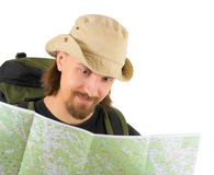 Smiling backpacker in hat looking into his map. Over white Royalty Free Stock Image