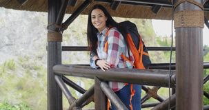 Smiling backpacker on a mountain lookout stock video footage