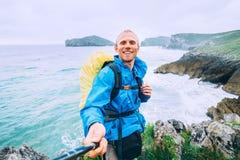 Smiling backpakcer traveler take selfie photo on ocean coast stock image