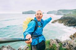 Smiling backpakcer traveler take selfie photo on ocean coast royalty free stock photo