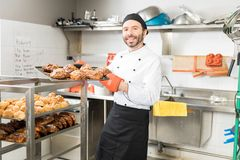 Smiling Baker With Baked Pastries In Restaurant Kitchen. Skilled mid adult chef showing yummy pastries in professional kitchen stock images