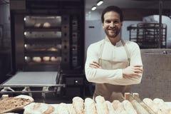 Smiling Baker in Bakery Department in Supermarket. Bearded Man in Apron. Fresh Bread. Worker in Hypermarket. Worker of Supermarket Concept. Loaf of Bread Stock Image