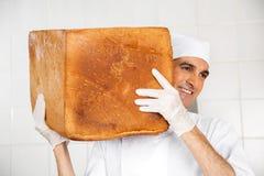 Smiling Baker Carrying Big Bread Loaf On Shoulder stock photography