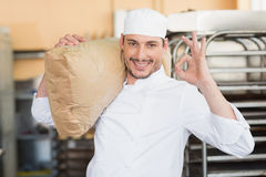 Smiling baker holding bag of flour Royalty Free Stock Photography