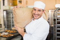 Smiling baker holding bag of flour Stock Photography