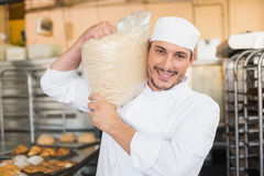 Smiling baker holding bag of rising dough Stock Images