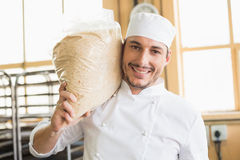 Smiling baker holding bag of rising dough Royalty Free Stock Photos