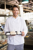 Smiling baker holding meringue tray Royalty Free Stock Images