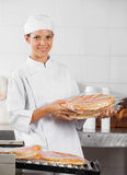 Smiling Baker Holding Packed Pizza Breads Stock Photography