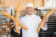 Smiling baker holding three baguettes Royalty Free Stock Photos