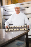 Smiling baker holding tray of raw dough Stock Image