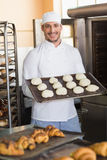 Smiling baker holding tray of raw dough Royalty Free Stock Image