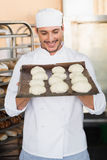 Smiling baker holding tray of raw dough Royalty Free Stock Photography