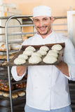 Smiling baker holding tray of raw dough Royalty Free Stock Images