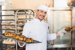 Smiling baker holding trays of croissants Royalty Free Stock Images