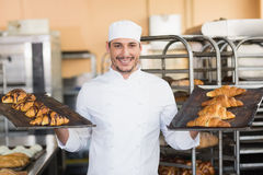 Smiling baker holding trays of croissants Stock Photos