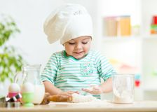 Smiling baker kid girl in chef hat Stock Image