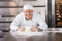 Smiling baker kneading dough on counter Stock Images