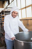 Smiling baker leaning on industrial mixer Royalty Free Stock Image