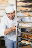 Smiling baker pushing tray of bread Royalty Free Stock Photo