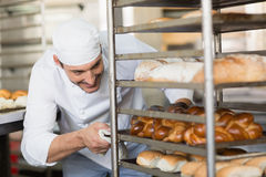 Smiling baker pushing tray of bread Royalty Free Stock Photos