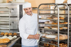 Smiling baker pushing tray of bread Stock Photo