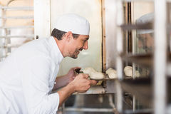Smiling baker putting dough in oven Royalty Free Stock Image