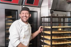 Smiling Baker putting a rack of pastries into the oven in bakery or pastry shop. stock photos