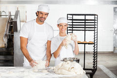 Smiling Baker's Kneading Dough Together In Bakery Royalty Free Stock Image