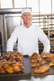 Smiling baker showing board of breads Royalty Free Stock Photo