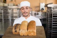 Smiling baker showing loaves of bread Stock Photography