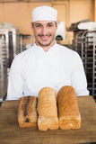Smiling baker showing loaves of bread Stock Photo