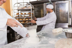 Smiling baker sieving flour on the dough. In the kitchen of the bakery Royalty Free Stock Photos